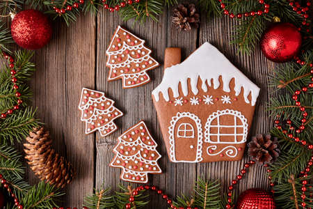 fur tree: Christmas gingerbread house and fur tree cookies composition with xmas decorations on vintage wooden table background. Homemade traditional dessert food recipe. Rustic style. Stock Photo