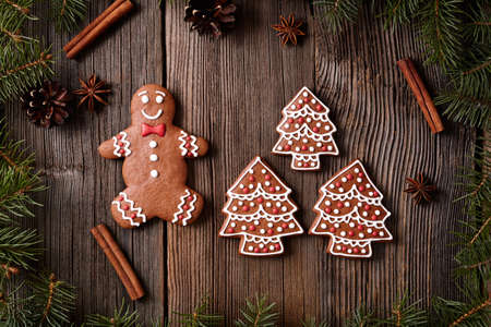 fur trees: Christmas gingerbread cookies man and fur trees composition in xmas decorations frame on vintage wooden table background. Traditional homemade biscuit dessert recipe. Rustic style.