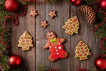 fur trees: Christmas gingerbread man, stars and fur trees cookies composition in xmas decorations frame on vintage wooden background. Top view. Traditional homemade holiday celebration recipe. Rustic style. Stock Photo