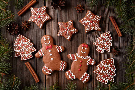 fur trees: Gingerbread man and woman couple, fur trees, star, christmas cookies composition with xmas tree decoration on vintage wooden table background. Homemade tradition new year dessert food recipe. Rustic style Stock Photo