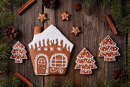 fur trees: Gingerbread cookies house stars and fur trees in new year composition frame. Homemade traditional christmas  dessert recipe. Rustic style. Stock Photo