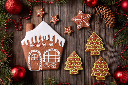 fur trees: Gingerbread house, stars and fur trees cookies christmas composition in new year decorations frame on vintage wooden table background. Homemade traditional dessert icing recipe. Top view. Rustic style.