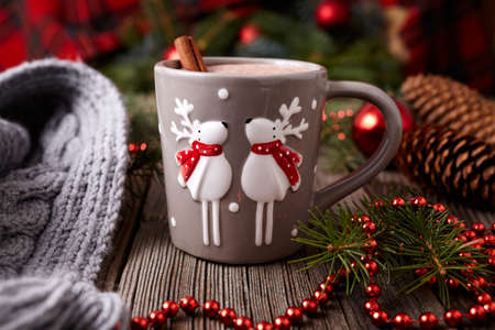 Cup of hot chocolate or cocoa with two cute deer and cinnamon in new year tree decorations frame on vintage wooden table background. Homemade traditional celebration recipe. Rustic style.