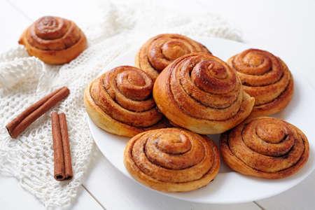 Sweet cinnamon bun rolls christmas delicious dessert on white vintage table. Traditional swedish kanelbullar baked pastry Archivio Fotografico
