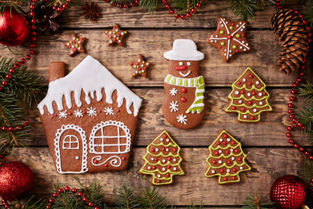 fur trees: Gingerbread house, fur trees, stars and snowman cookies christmas composition in new year decorations frame on vintage wooden table background. Top view. Homemade traditional recipe. Rustic style.