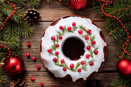Traditional homemade christmas cake holiday dessert with cranberry in new year tree decorations frame on vintage wooden table background. Rustic style. Top view Archivio Fotografico
