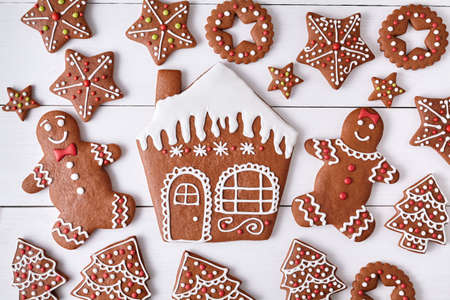 fur trees: Gingerbreand cookies christmas composition, house man and woman couple, stars, fur trees on white wooden table background. New year traditional dessert food. Top view. Rustic style.