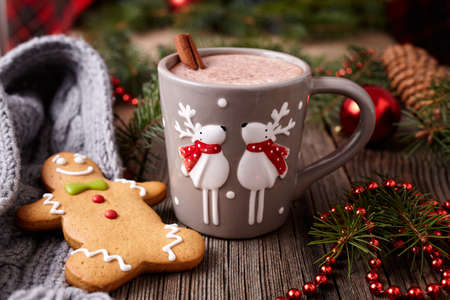 Cup of hot chocolate or cocoa drink with two cute deer, cinnamon and gingerbread man christmas cookies in new year tree decorations frame on vintage wooden table background. Homemade traditional celebration dessert recipe