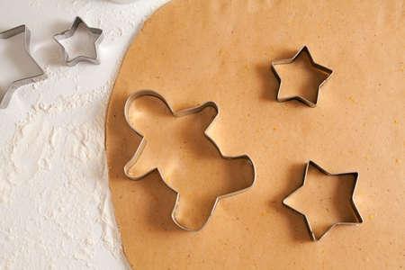 decoracion de pasteles: Caseras galletas de jengibre tradicional de la masa preparación receta de mesa de la cocina blanca con formas de corte y harina. Foto de archivo