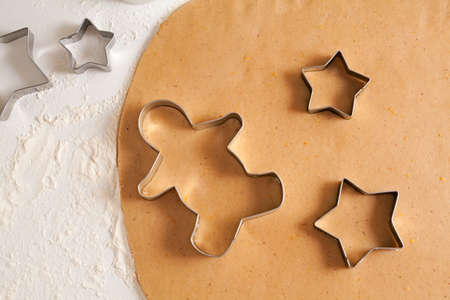 decorating christmas tree: Homemade traditional gingerbread cookies dough preparation recipe on white kitchen table with cutting forms and flour. Stock Photo