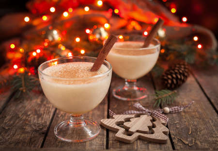 traditional celebrations: Eggnog traditional christmas egg, vanilla rum alcohol drink liqueur preparation recipe in two glass cups with cinnamon sticks on wooden vintage table. Red bokeh background.