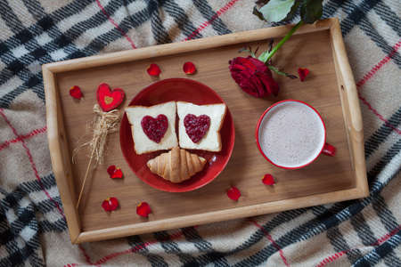 Valentines day breakfast in bed sweet romantic present, red rose flower. Two toasts with jam and hot chocolate. Top view