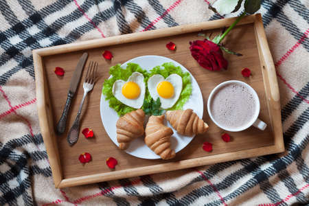 glass bed: Romantic breakfast in bed with heart-shaped eggs on salad, croissants, coffee, rose flower and petals on wooden tray. Top view
