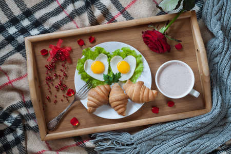 wooden bed: Delicious romantic breakfast in bed surprise with heart-shaped eggs, jam toasts, croissants, rose flower and petals on wooden tray table. Valentines day healthy meal concept. Top view.