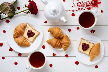 love shape: Romantic breakfast for Valentines day with toasts, heart shaped jam, croissants, rose petals and tea on white wooden table background. Concept of romantic love. Top view Stock Photo