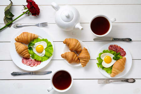 foe: Romantic breakfast for two with heart shaped eggs, salad, croissants, rose flower and black tea on white wooden table background. Food concept of love foe Valentines day. Top view Stock Photo