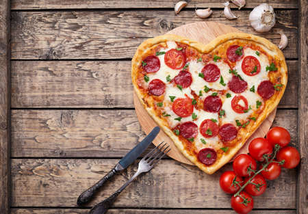 Heart shaped pizza with pepperoni, tomatoes and mozzarella on vintage wooden table background. Valentines day love concept.  Top view.
