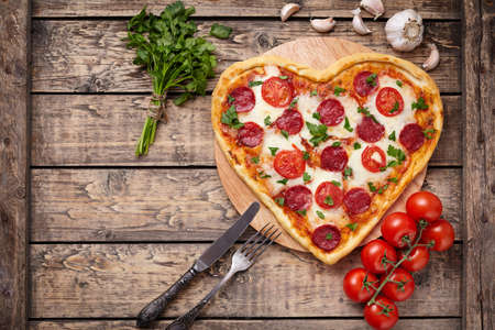 pizza: Valentines day heart shaped pizza with pepperoni, cherry tomatoes, mozzarella and parsley on vintage wooden table background. Symbol of love. Rustic style, Top view.