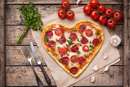Heart shaped pizza for Valentines day with pepperoni, mozzarella, tomatoes, parsley and garlic on vintage wooden table background. Food symbol of romantic love.  Rustic style. Top View.