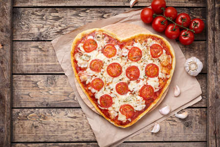 Heart shaped pizza margherita with tomatoes, mozzarella and garlic on vintage wooden table background. Symbol of vegetarian romantic love. Rustic style, top view. Archivio Fotografico