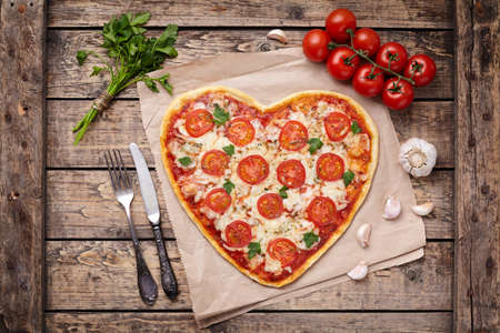 Heart shaped pizza margherita love concept for Valentines Day with mozzarella, tomatoes, parsley and garlic on vintage wooden table background. Rustic style and top view.