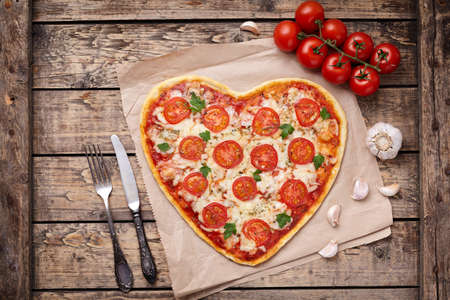 Vegetarian heart shaped pizza margherita with tomatoes, mozzarella, parsley and garlic on vintage wooden table background. Food concept of romantic love. Rustic style and natural light.