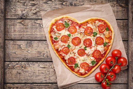 shape: Heart shaped pizza margherita with tomatoes and mozzarella vegetarian meal on vintage wooden table background. Food concept of romantic love for Valentines Day. Rustic style and natural light. Stock Photo