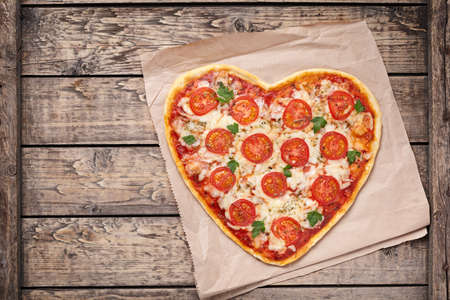 Heart shaped pizza margherita with tomatoes and mozzarella for Valentines Day on vintage wooden background. Food concept of romantic love. Rustic style, top view.