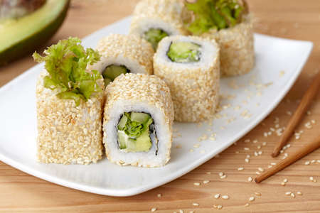 vegetarian cuisine: California vegetarian sushi roll with avocado, cucumber and salad. Traditional Japanese rice sushi healthy seafood. White plate, wooden table background. Stock Photo