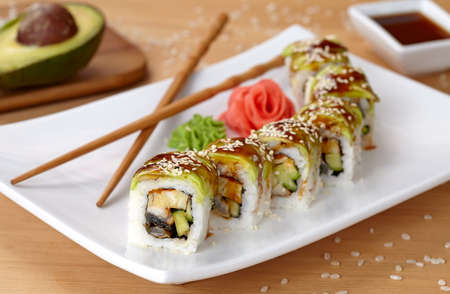 black and white dragon: Green dragon sushi roll with eel, avocado, cucumber, wasabi and ginger. Traditional asian rice sushi healthy seafood. White plate, wooden table background.