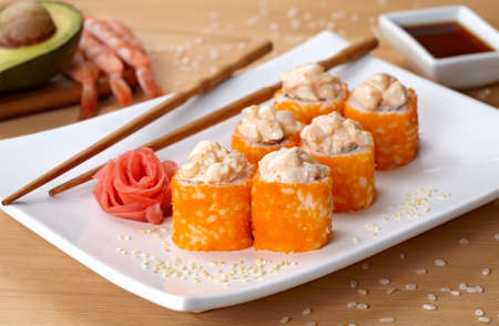 deluxe: California deluxe sushi roll with tobiko caviar and spice. Traditional asian rice sushi healthy seafood. White plate, wooden table background.