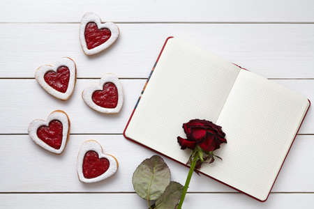 Handmade heart shaped cookies with empty notebook and rose flower on white wooden background. Valentines day food concept of romantic love. Top view, flat lay.