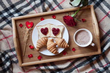 Romantic breakfast in bed for Valentines Day. Toasts with jam, croissants, hot chocolate, red rose flower and petals on wooden tray table. Concept of romantic love. Top view flat lay