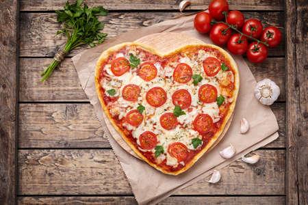 Cuore di pizza a forma di margherita concetto di amore vegetariano con mozzarella, pomodori, prezzemolo e aglio sul tavolo d'epoca sfondo di legno. cibo San Valentino. Stile rustico, vista dall'alto, distesi. Archivio Fotografico - 52215874