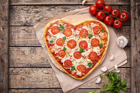 pizza crust: Heart shaped pizza margherita vegetarian love concept with mozzarella, tomatoes, parsley and garlic composition on vintage wooden table background. Valentines Day food. Rustic style, top view, flat lay.