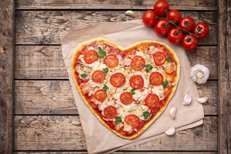 cherry tomatoes: Heart shaped pizza margherita love food symbol with mozzarella, tomatoes, parsley, and garlic composition on cutting board, vintage wooden table background. Valentines Day food. Rustic style, top view, flat lay.