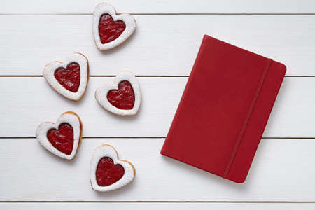 composition notebook: Heart shaped cookies with empty red notebook, composition on white wooden background for Valentines day. Food concept of romantic love. Top view, flat lay. Stock Photo