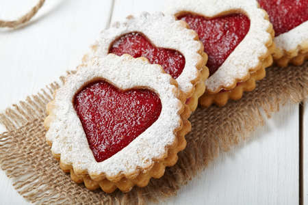 Round shortbread cookies with heart shaped jam close-up composition for Valentines Day on vintage wooden background. Food concept of romantic love