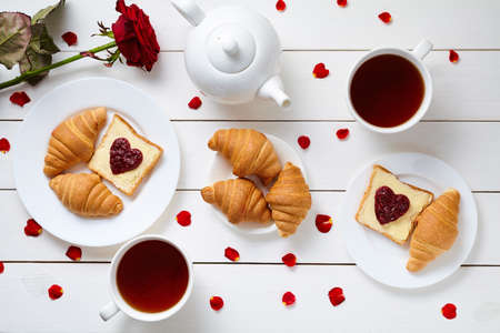 Breakfast for couple on Valentines Day with toasts, heart shaped jam, croissants, red rose flower, petals and tea composition on white wooden table background. Food concept of love. Top view.