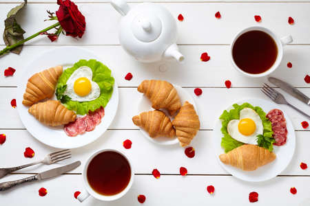Breakfast for couple on Valentines day with heart shaped fried eggs, salad, croissants, salami sausage, rose petals composition and tea on white wooden table background. Concept of romantic love. Top view, flat lay.