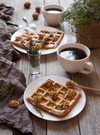 kinfolk: Belgian waffles breakfast with nuts, honey, herbs and coffee. Bright mood food. Rustic style, natural light.
