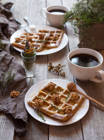Belgian waffles sweet healthy dessert with honey, nuts, coffee and herbs. Bright morning mood food. Vintage wooden background, rustic kinfolk style.