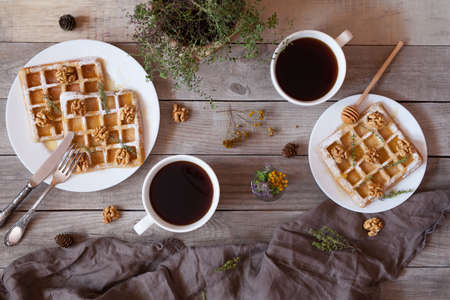 kinfolk: Waffles with honey, nuts, coffee and herbs, sweet dessert breakfast. Bight morning mood food. Vintage wooden table background, rustic kinfolk style. Top view