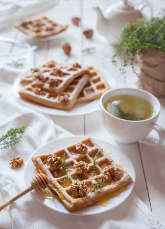 kinfolk: Belgian waffles sweet healthy dessert with honey, nuts, green tea and herbs. Bright morning mood food. Vintage white wooden table background, rustic kinfolk style. Stock Photo