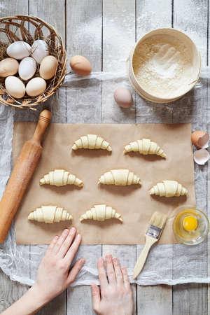 Chef-kok die ruwe croissants op perkament, bereidingsproces. Onherkenbaar handen te bereiden deeg voor croissant zoete traditionele dessert. Bovenaanzicht rustieke stijl. Stockfoto - 54747454