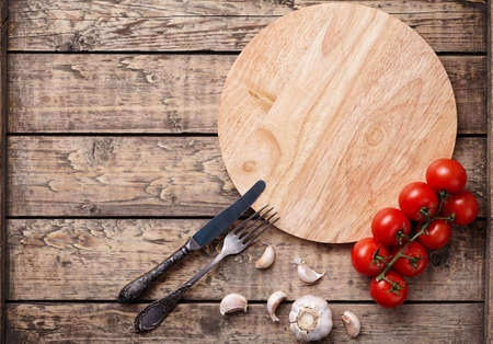 display board: Pizza cutting board template with empty space for design text. Round wooden plate with tomatoes on vintage wooden background. Top view rustic style. Stock Photo