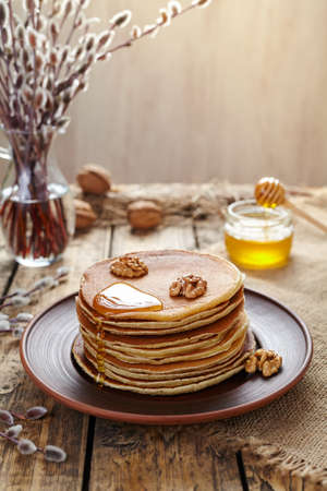 american dessert: Stack of pancakes with flowing honey and nuts on vintage wooden table background. Traditional American dessert. Rustic style.