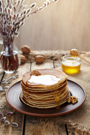american dessert: Stack of traditional American pancakes with flowing honey and nuts on vintage wooden table background. Homemade delicious dessert. Rustic style. Stock Photo