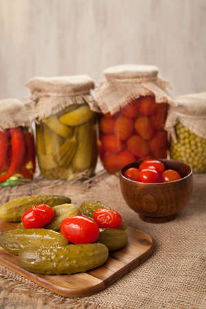 larder: Pickled preserved homemade vegetables in glass transparent jars, cucumbers, pepper, tomatoes and peas on vintage table background