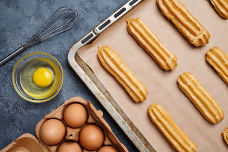 profiterole: Eclairs or profiterole preparing recipe with eggs on baking sheet background. Top view. Stock Photo